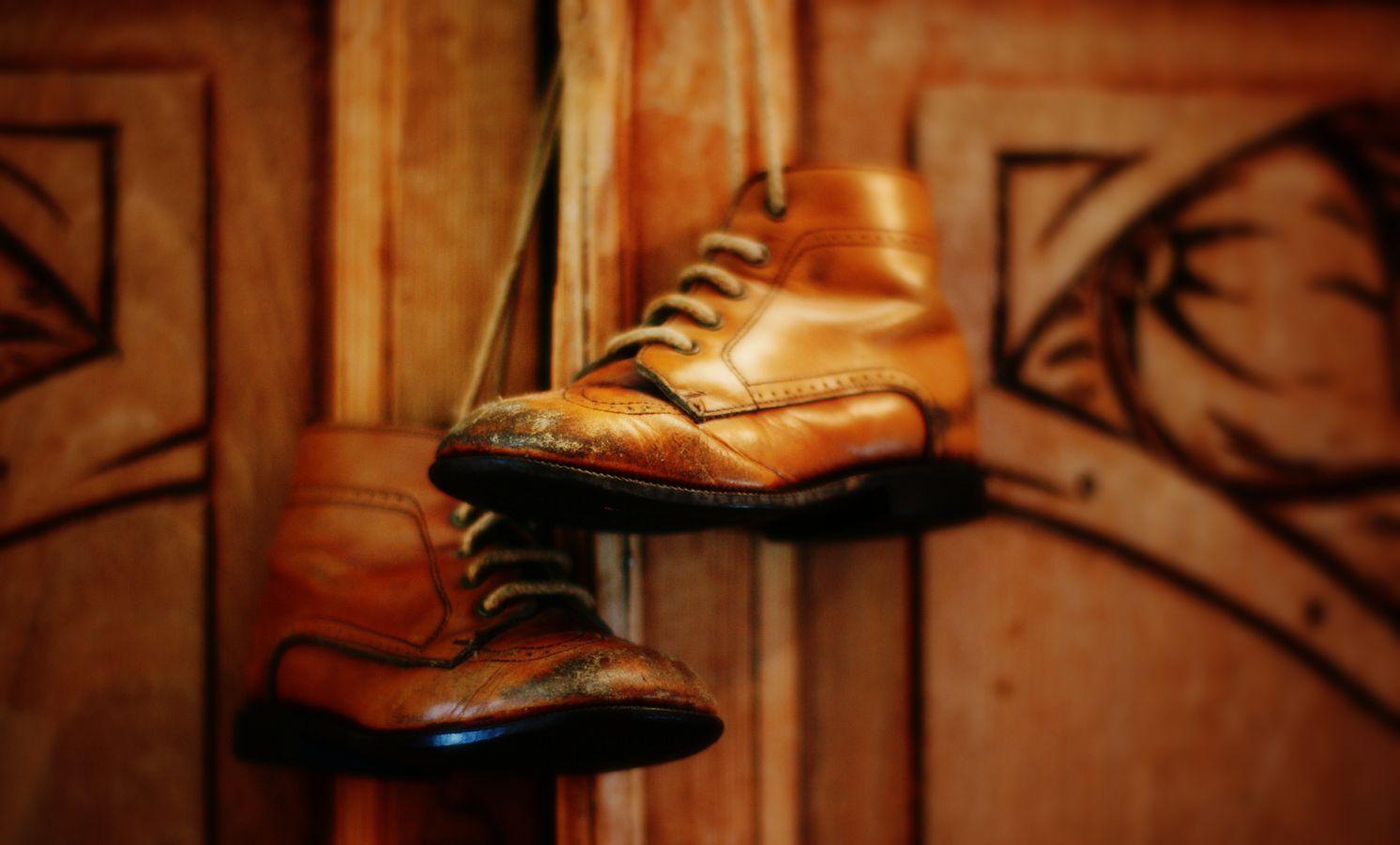 Une paire de veille chaussures d'enfant en cuir, usées au bout suspendue devant un buffet en bois de la même couleur.