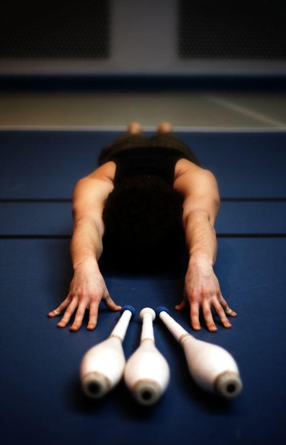 Martin, en plein échauffement, est à plat ventre sur le sol du gymnase. Ses mains, tendues vers l'objectif, sont placées de chaque côté de sa triplette de massues.