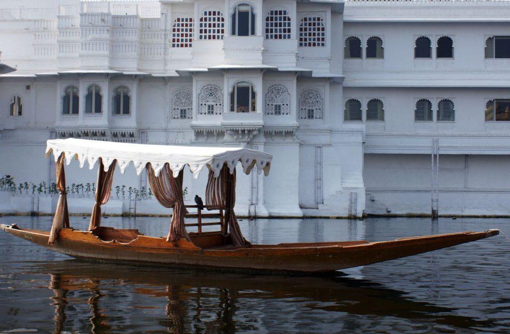 Un pigeon est posé sur un bateau en bois avec un baldaquin blanc. En arrière plan le palace flottant d'Udaipur au Rajasthan, Inde.