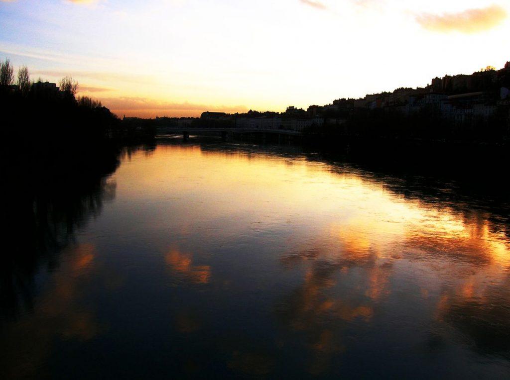 Un ciel nuageux, éclairé par le couché de soleil, se reflète dans le Rhône à Lyon. Le dôme rond de l'Opéra de Lyon émerge au milieu des autres bâtiments.