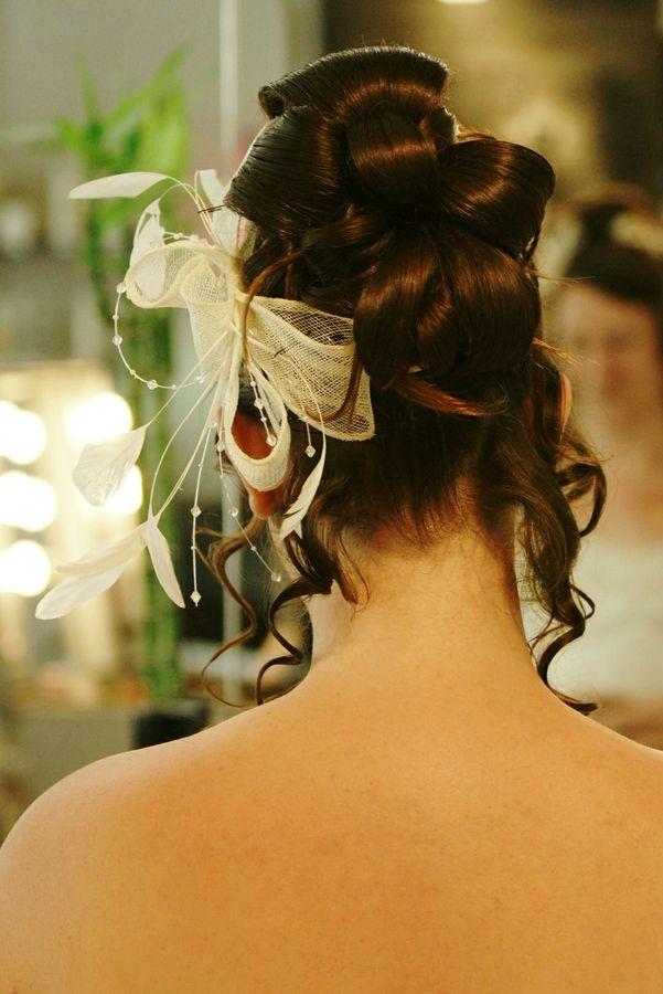 Chloé se fait faire son chignon de mariage dans un salon de coiffure à Saint Etienne. Il est décoré avec un ruban et des plumes blanches.