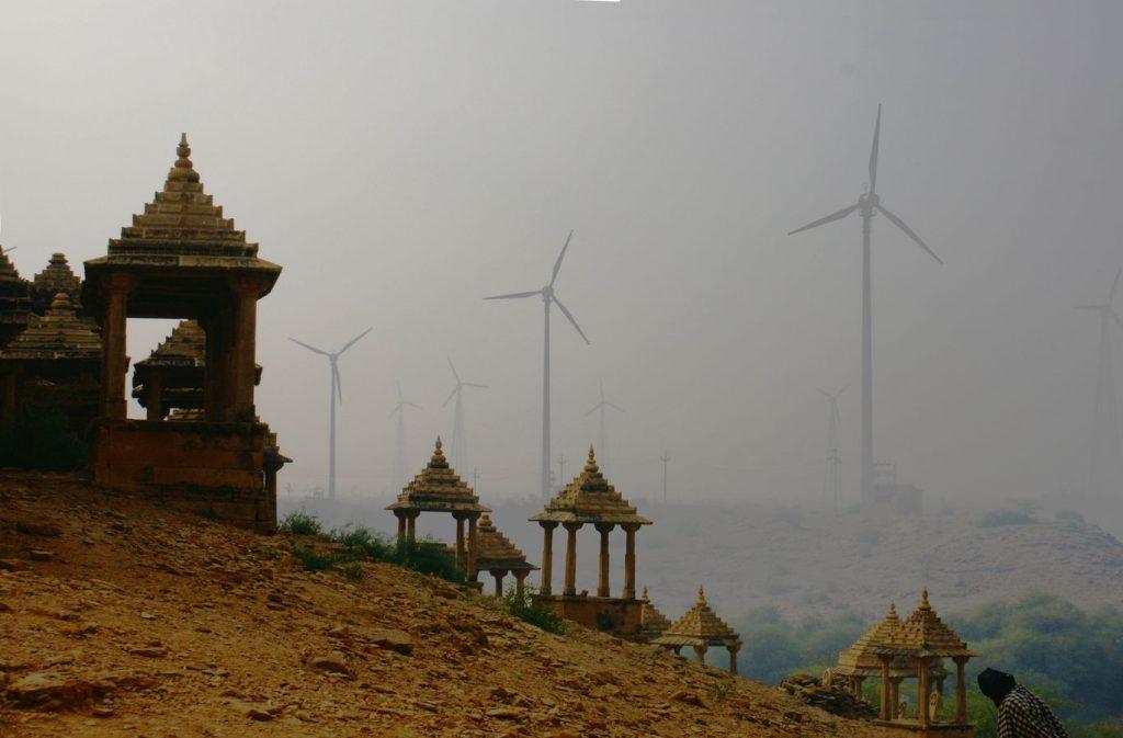 Les cénotaphes des Maharawal de la nécropole de Bada Bagh sont à côté de Jaisalmer. Derrières ces mausolées anciens se dressent des éoliennes dans la brume.