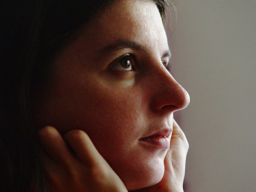 Portrait d'Anne à le regard perdu dans ses pensées. Elle tient sa tête avec ses mains repliés et une douce lumière lui éclaire le visage.