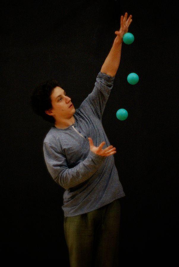 Martin pratique la jonglerie avec trois balles au plateau 4 des Subsistances. Les balles forment un arc de cercle entre ses mains.