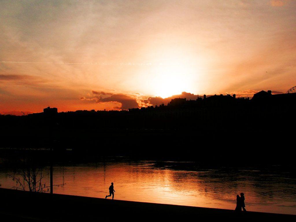 Le couché de soleil se reflète dans le Rhône à Lyon et une silhouette semble courir sur le fleuve. Un jeune couple s'enlace au bord de l'eau.