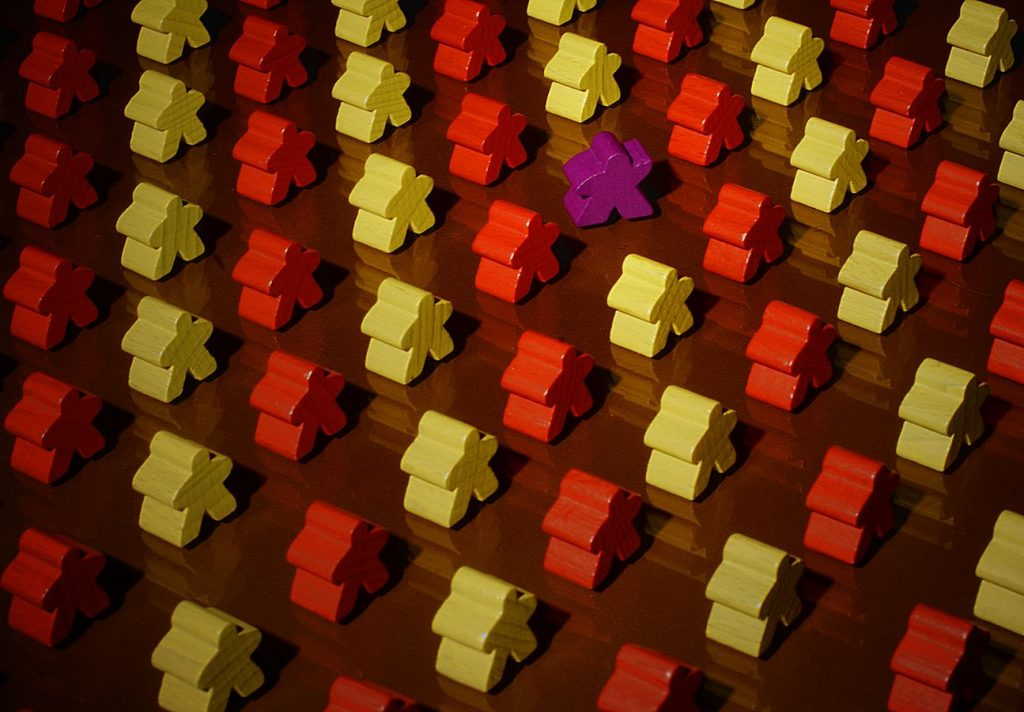 Des meeples formes des lignes jaunes et rouges sur une plaque de verre. Au milieu un meeple violet s'est décalé pour faire un coucou de la main.