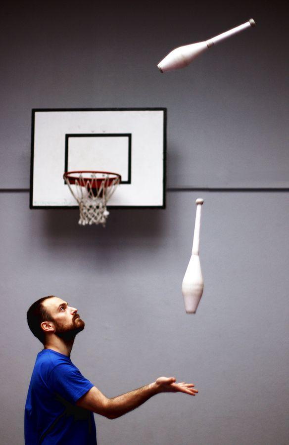 Alexander jongle avec des massues devant un panier de basket au gymnase d'Overground Circus à Lyon. On lit la concentration dans le regard du jongleur.