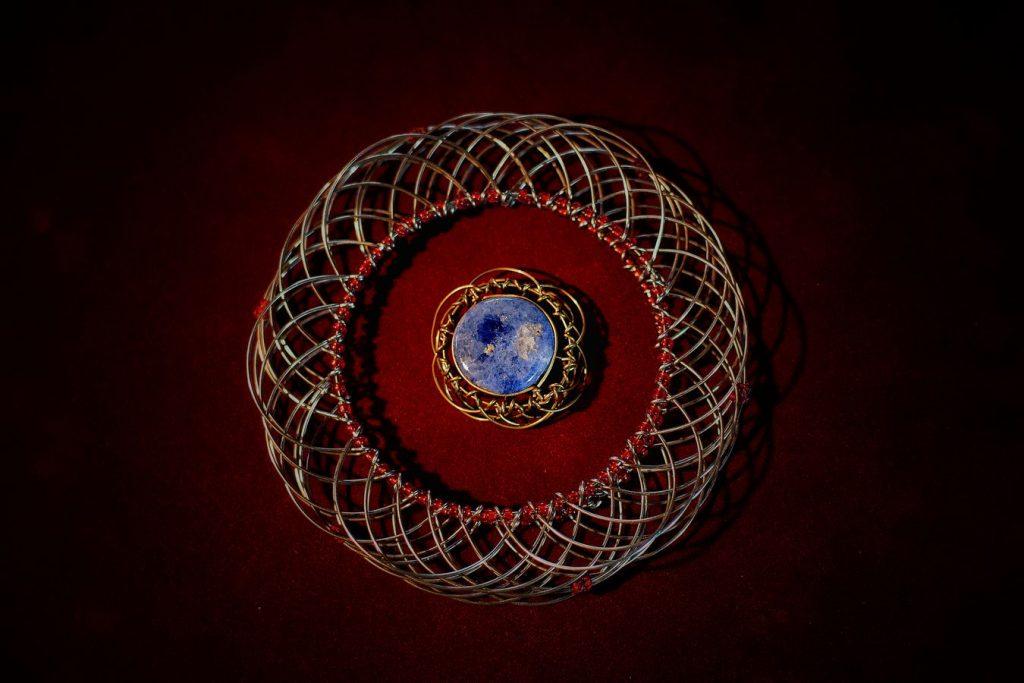 Un grand mandala en fils argentés reliés par des perles rouges entoure un plus petit avec une pierre bleue. Les deux bijoux sont posé sur un fond bordeaux.