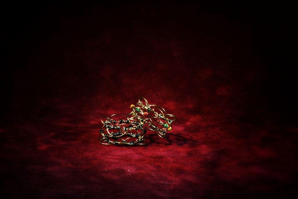 Deux bijoux sont posés sur un tapis de bridge en velours bordeaux .Le premier manada est relié par des liens noir, le second par des perles colorés.
