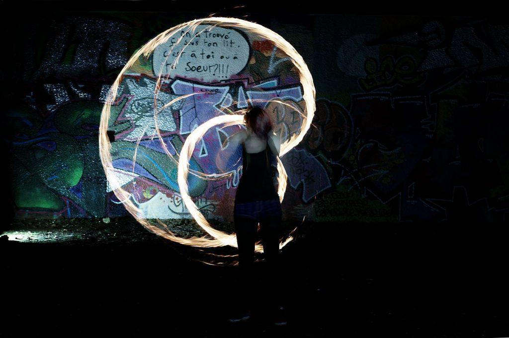 Johanna fait de la jonglerie aux Bolas de feu et dessine le symbole Yin avec ses poîs. L'intérieur du symbole est plus clair.