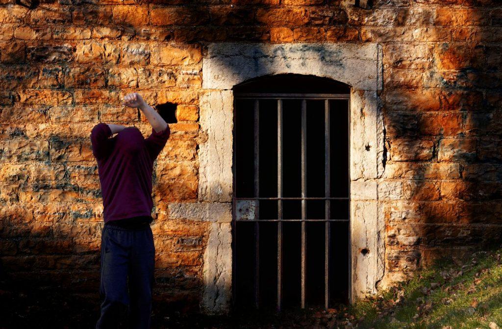 Pour marquer son enfermement, Martin cache son visage dans son pull devant la grille de sa prison en extérieur au fort de Montessuy à Caluire-et-Cuire.