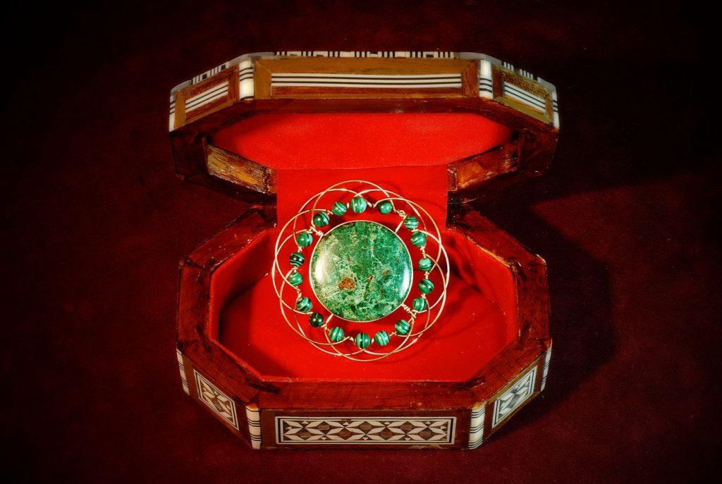 Mandala manufacturé par Jonas avec une pierre verte sertie en son centre. Le bijou repose dans un écrin nacré garni de velours rouge.