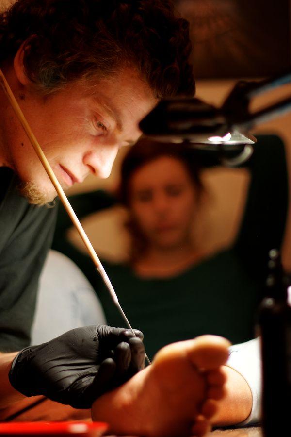 Séance de tatouage par Jonas, il réalise une rose de vents sur la cheville de Clémence que l'on peut voir, floue, en arrière plan.