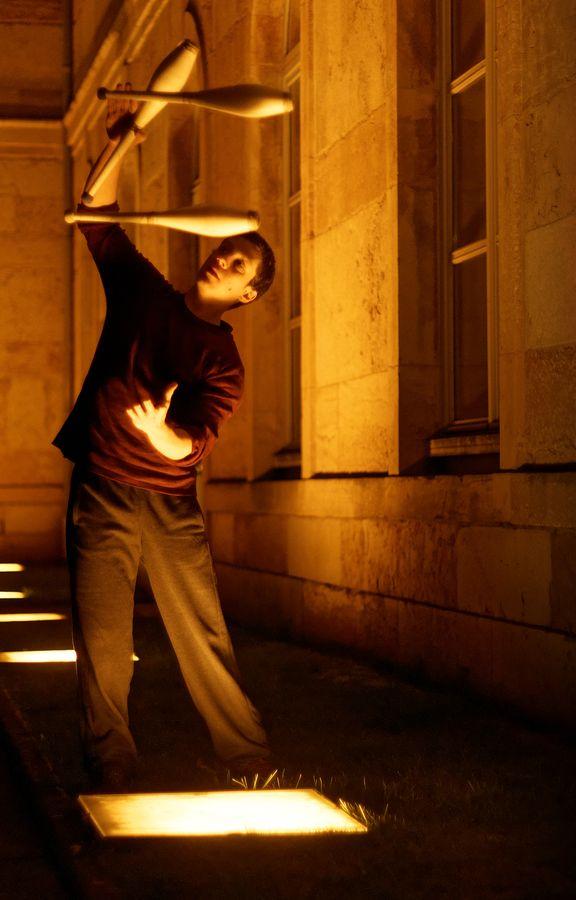 Martin fait de la jonglerie à 3 massues derrière l'Hôtel de ville de Caluire-et-Cuire. Il est éclairé par les projecteurs au sol.