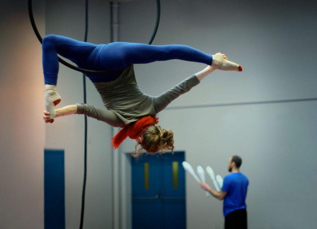 Gabrielle s'entraine au cerceau aérien à Overground Circus, Alexander s'apprête à jongler à 4 massues. Il fait froid, Gabrielle porte une écharpe rouge.