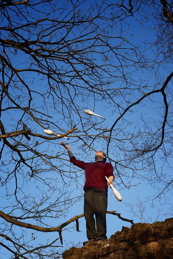Martin fait de la jonglerie à trois massues au milieu des branches, en haut d'un monticule, au fort de Montessuy, à Caluire-et-Cuire.