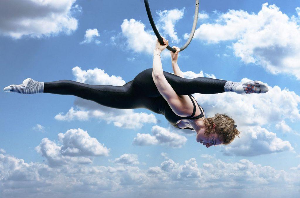 Gabrielle est suspendue par les mains à son cerceau aérien au gymnase d'Overground Circus. Elle est en grand-écart et sa jambe passe derrière son épaule.