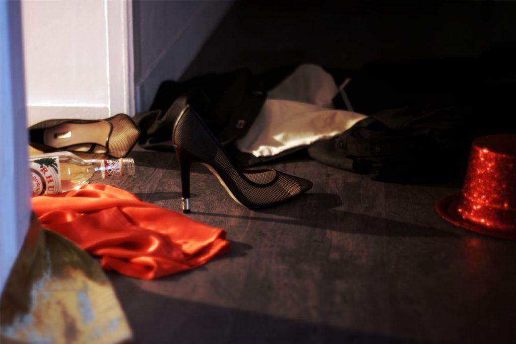 A l'entrée d'une chambre, des vêtements d'homme et de femme sont par terre dont une paire de talons aiguilles. Il y a aussi une bouteille d'alcool ouverte.