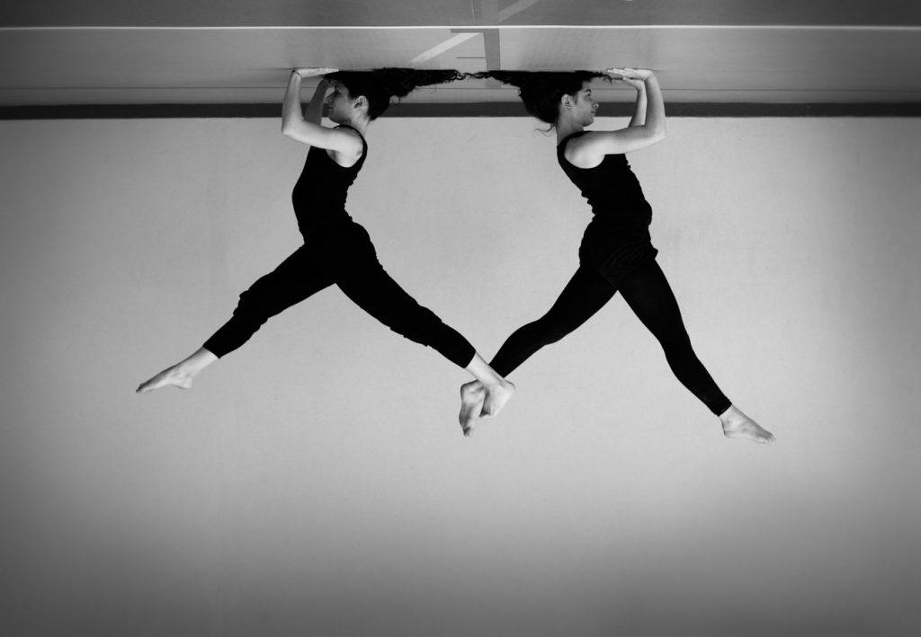 Julie et Mathilde, en trépied à Overground Circus, se retiennent par la jambe. Cette photo d'acrobatie, en noir et blanc, est présentée la tête en bas.