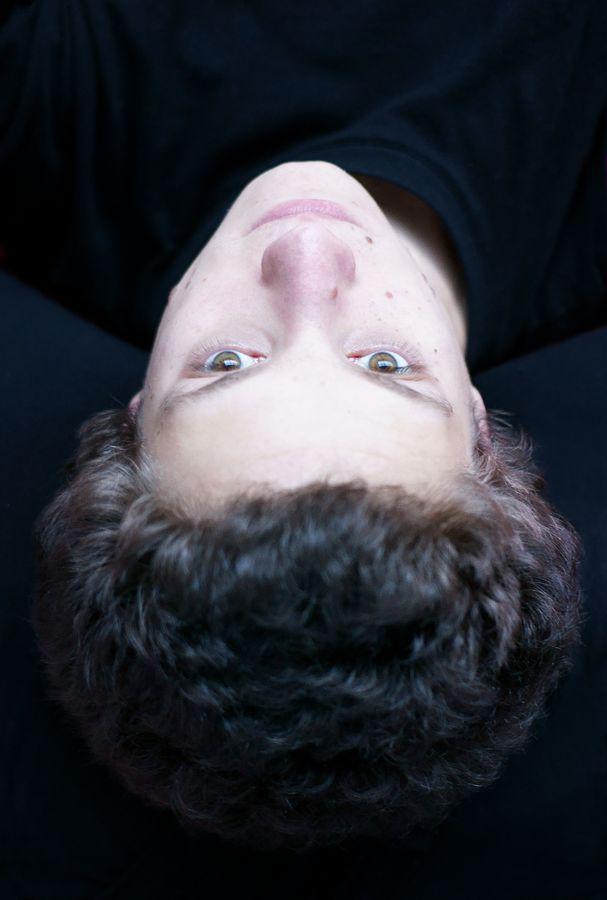Portrait de Martin, il est couché sur le dos la tête vers l'objectif et regarde le ciel à travers la verrière du gymnase d'Overground Circus.