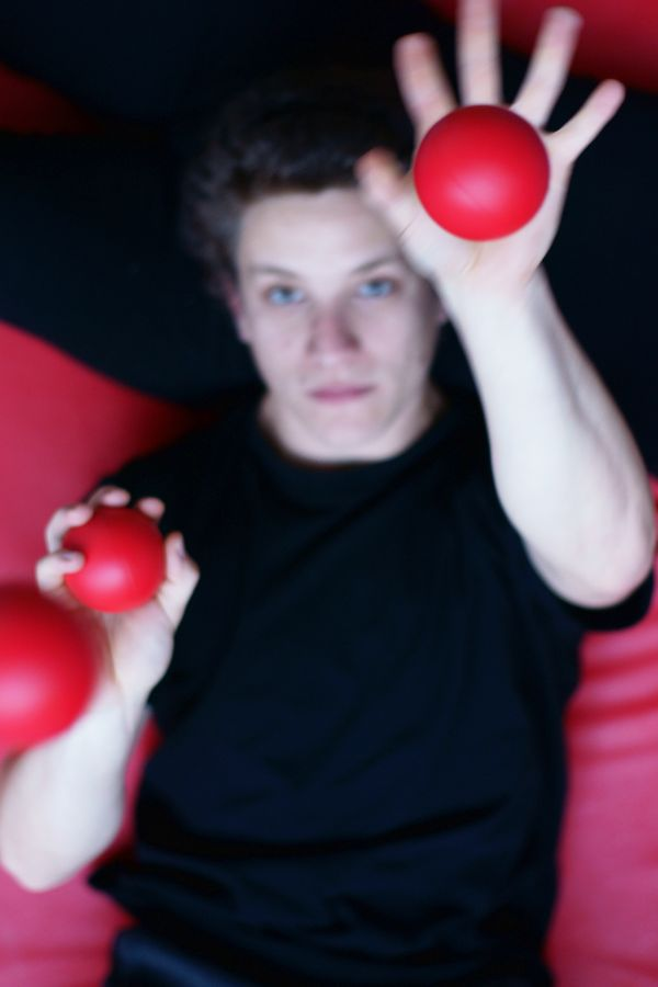 Martin pratique la jonglerie à plat dos avec des balles rouges sur un tapis du gymnase d'Overground Circus. Seule la balle la plus haute est nette.