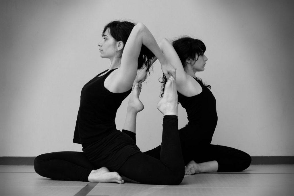 Mathilde et Julie font de l'acrobatie en miroir, chacune tient son pied par dessus son épaule. La photo en noir et blanc a été prise à Overground Circus.