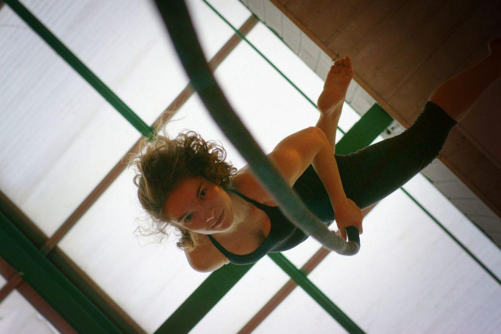 Margot fait de la corde lisse, La photo est prise d'en dessous. Au dessus d'elle, on voit la verrière du gymnase d'Overground Circus.