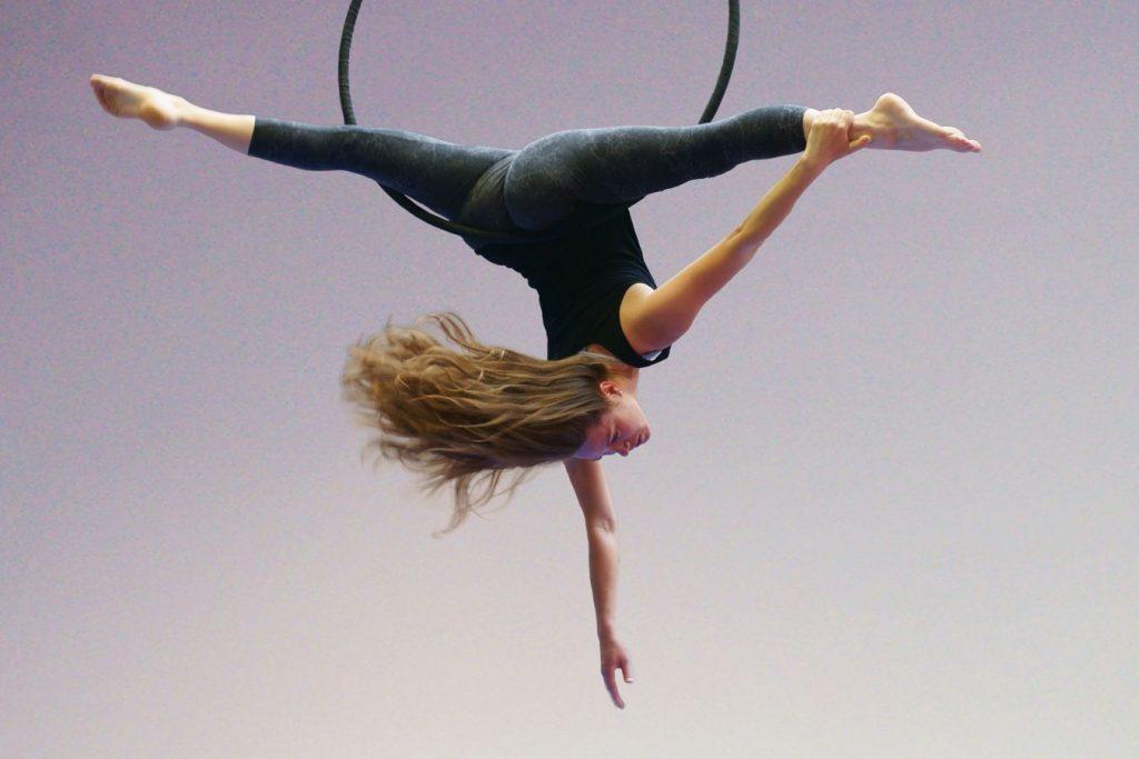 Audrey en grand-écart, au cerceau aérien au gymnase d'Overground Circus. Ces cheveux semblent flotter en l'air poussés par le vent.