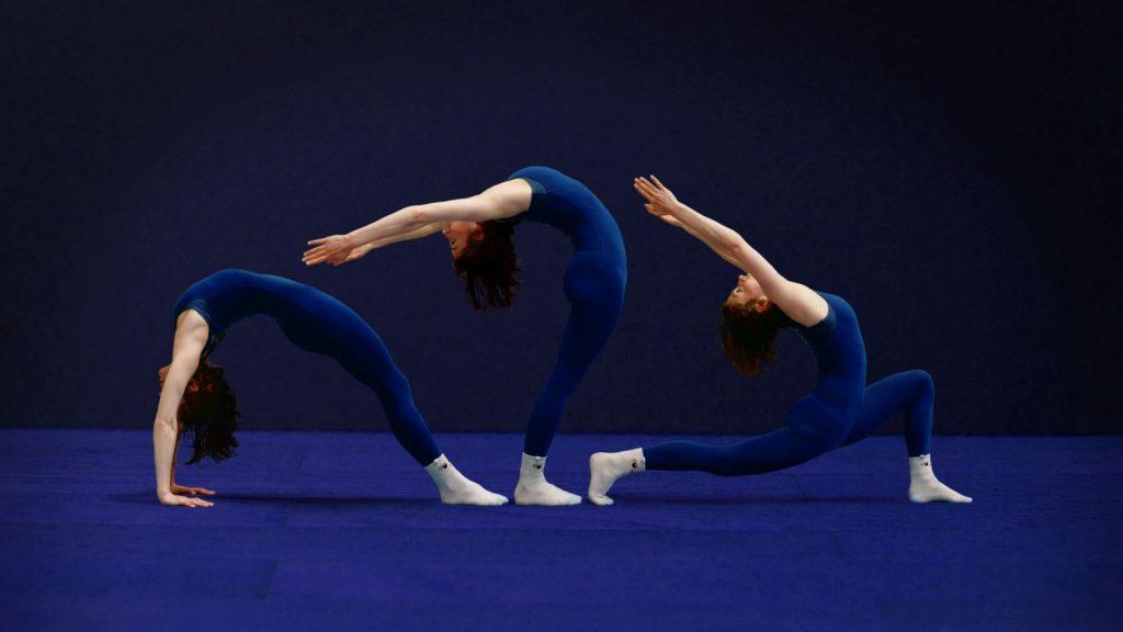 Gabrielle, en échauffement au gymnase d'Overground Circus utilise des positions de yoga. Trois positions sont visibles sur cette photo dans les tons bleus.