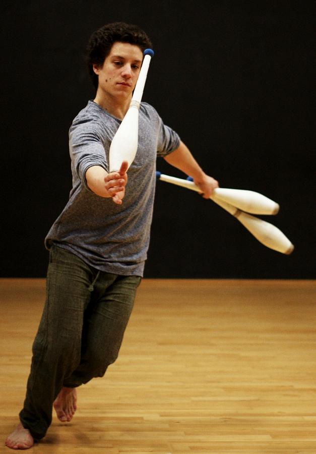 Pendant une session de jonglerie au Subsistances, Martin court sur le parquet avec une massue en équilibre sur le poignet.