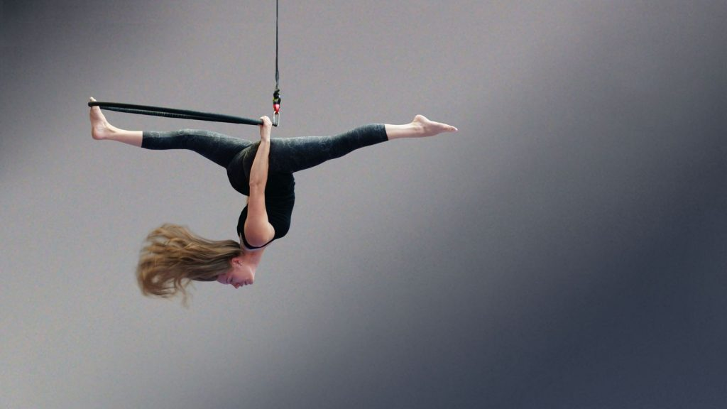 Audrey en grand-écart suspendue à son cerceau aérien au gymnase d'Overground Circus. Ces cheveux semblent flotter en l'air poussés par le vent.