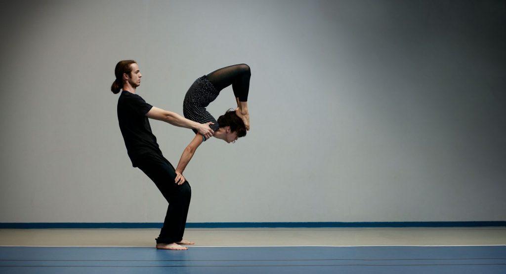 Des AcroGones en entrainement au gymnase d'Overground. Julie est en équilibre sur les genoux de Victor avec les pieds sur la tête en souplesse arrière.