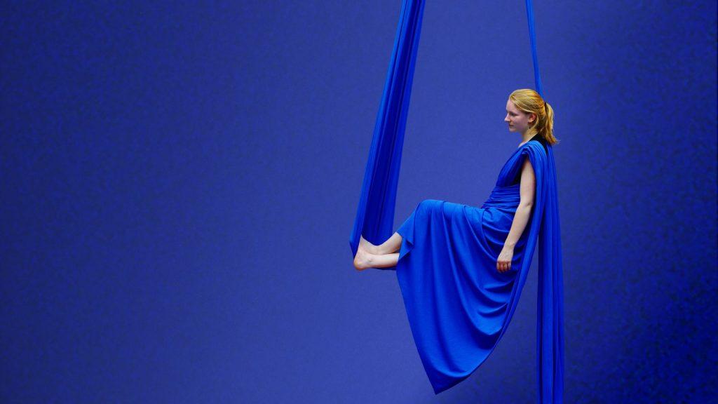 Vanille est assise en suspension dans un tissu aérien au gymnase d'Overground Circus. Le tissu bleu est replié en forme de robe.