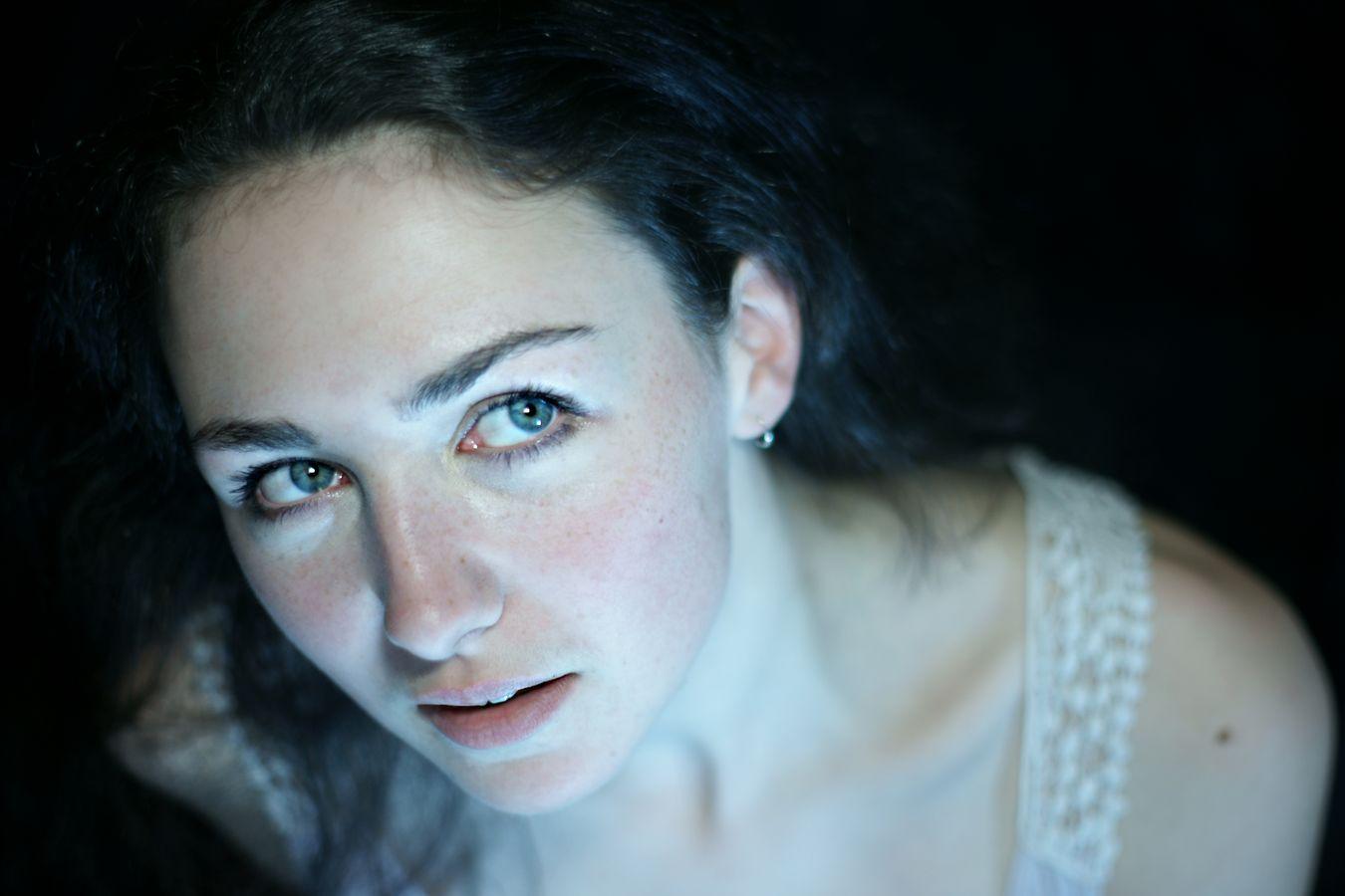 Portrait d'Iris qui porte un débardeur blanc avec de la guipure sur son épaule. Ses grands yeux bleus regardent sur le côté et elle ébauche un sourire.
