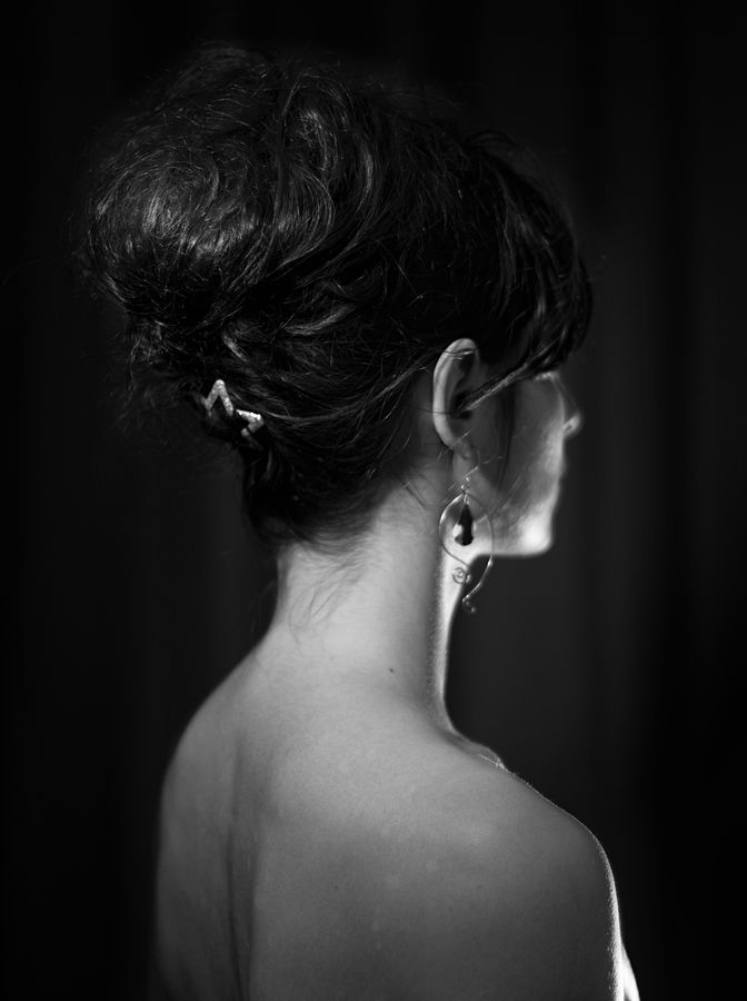 Portrait trois-quarts dos, noir et blanc, de Mathilde. Ces cheveux sont remontés sur sa nuque et maintenus par une barrette pailletée en forme d'étoile.