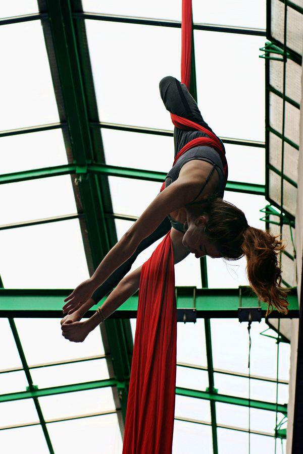 Margot fait du tissu aérien sous la verrière du gymnase d'Overground Circus. La circasienne est suspendue par la taille la tête en bas et tient son pied.