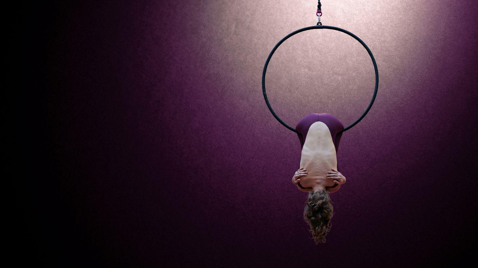 Gabrielle est suspendue à un cerceau aérien au gymnase d'Overground Circus à Lyon. Elle est de dos et porte un justaucorps violet avec un magnifique dos-nu.