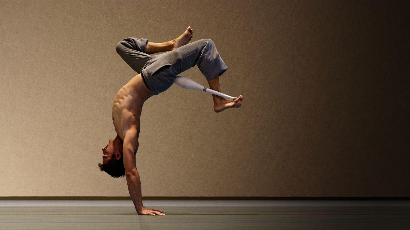 Joann, en entrainement de cirque au gymnase d'Overground Circus à Lyon, fait un équilibre en mexicain et a une massue coincée entre la cuisse et le pied.