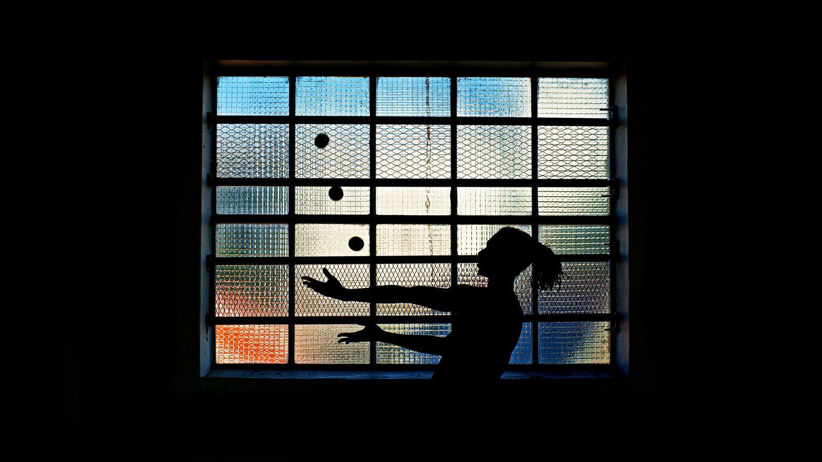 Jean-Souleyman, un jongleur lyonnais, jongle à trois balles devant une fenêtre à carreaux. La photo est prise en contre-jour et chaque balle a son carreau.
