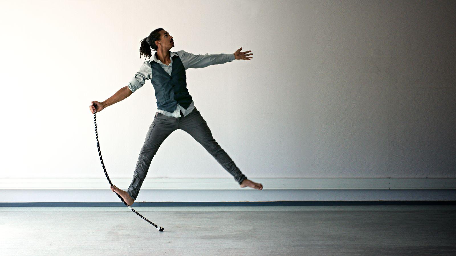 Jean-Souleymane fait une étoile à l'acrostaff. Cet acrobate au pieds-nus et en chemise a un pied sur le staff et étire son corps dans toutes les directions.