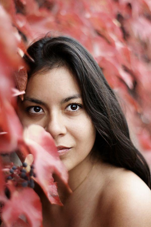 Portrait d'Ana devant une vigne rouge à Grézieu-la-Varenne. Son visage est enfoui dans les feuilles dont une recouvre partiellement son sourire.