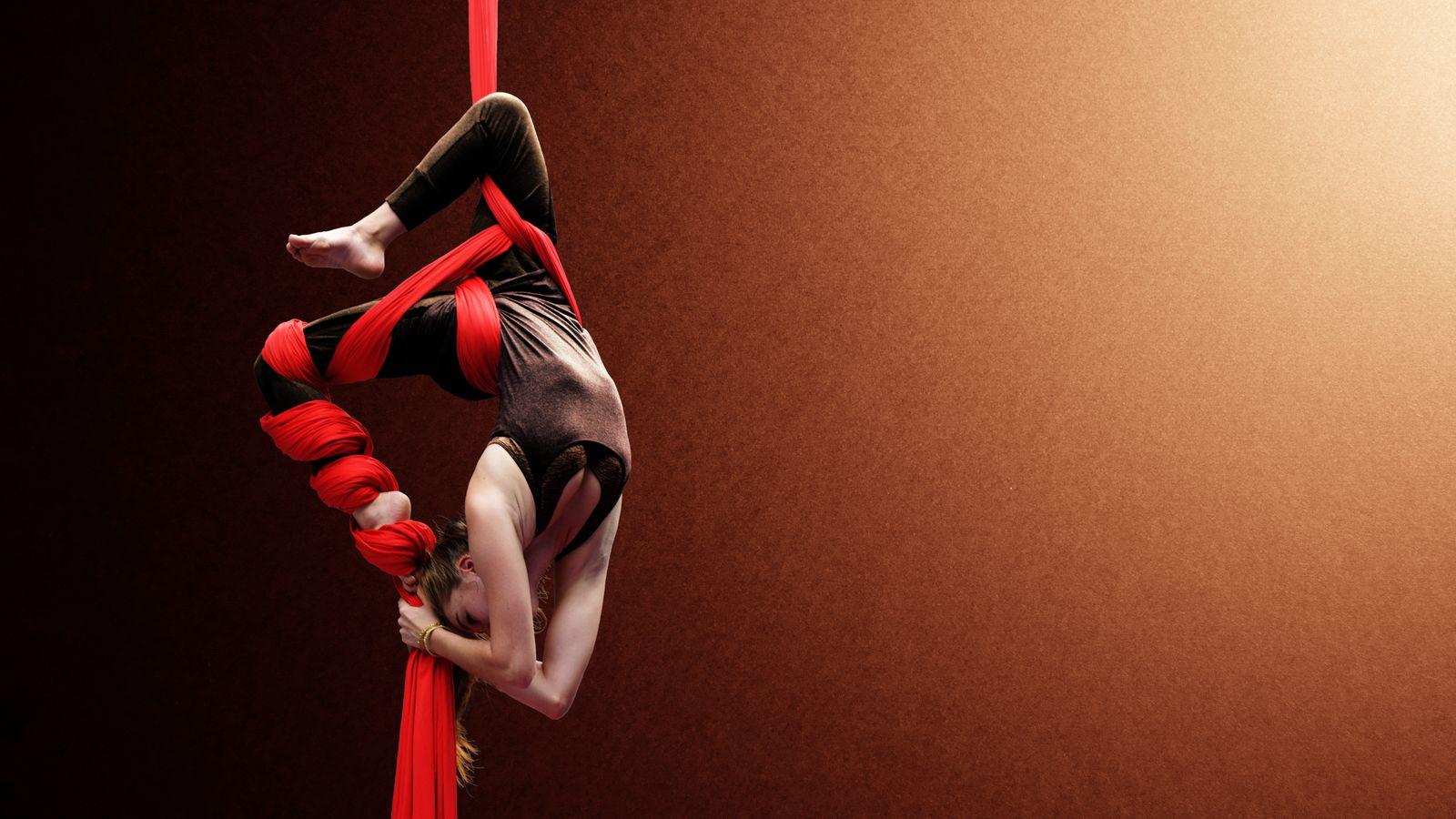 Margot est suspendue, en souplesse arrière, dans son tissu aérien, au gymnase d'Overground Circus à Lyon 5e. L'étoffe rouge est enroulée autour de sa jambe.