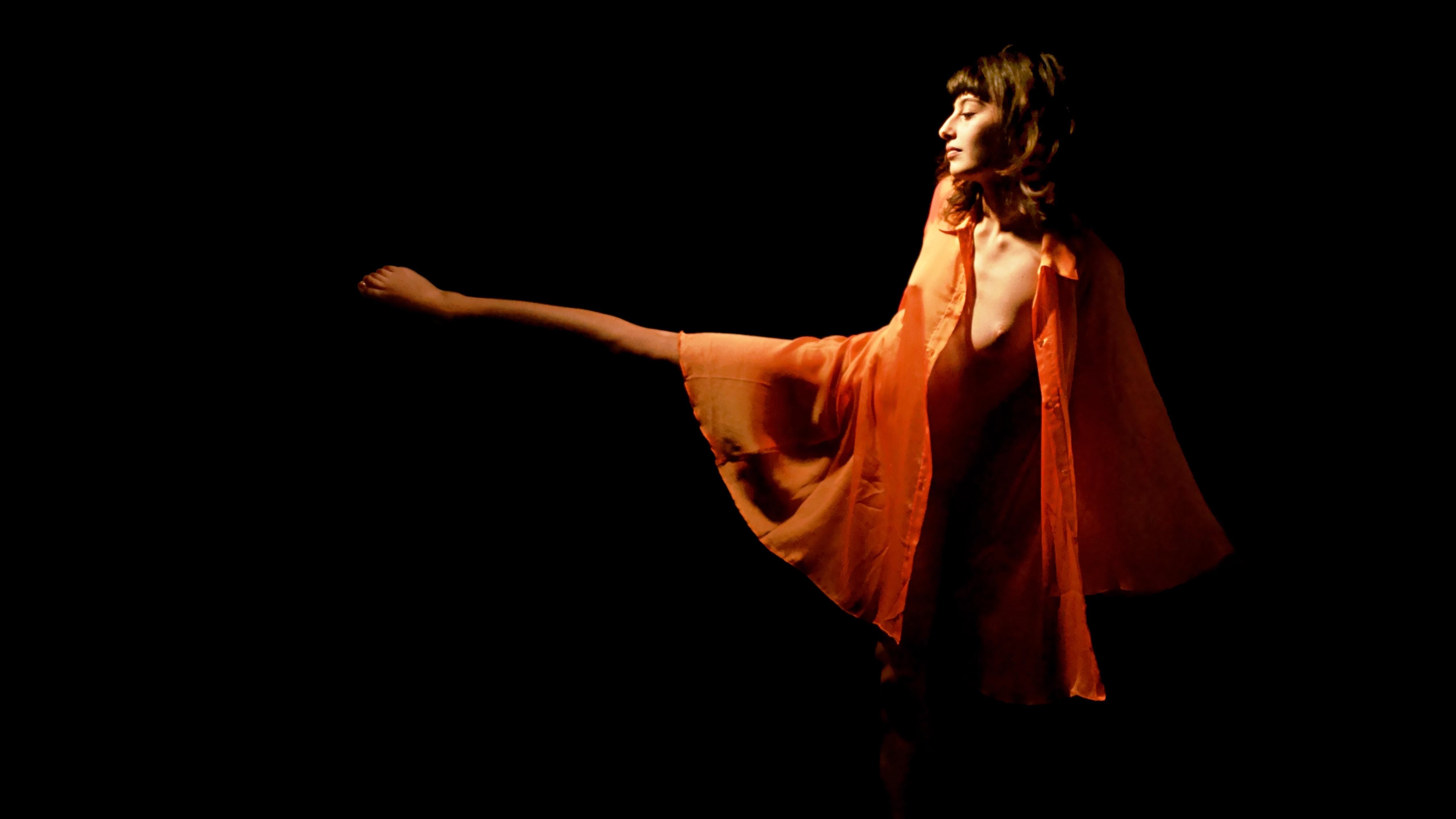 Maeva, nue sous une tunique orange transparente, danse. Sa jambe tendue sur le côté fait penser à une aiguille d'horloge enveloppée dans une cape orange.