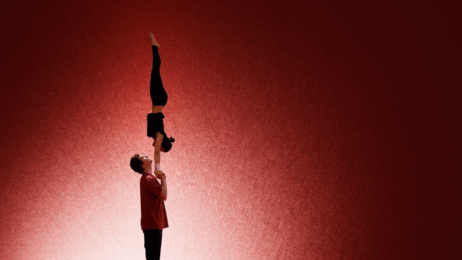 Iona et Jonas font un main-à-main au gymnase d'Overground Circus à Lyon 5e. Ils se sourient mutuellement dans cette photo de cirque tout en noir et rouge.