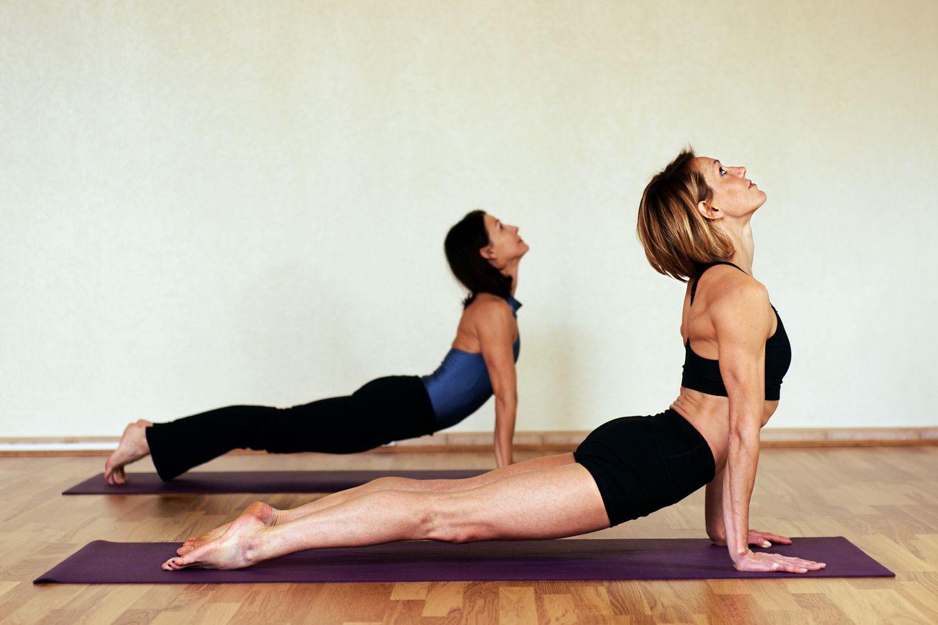 Sydney Martinie donne un cours individuel de Yoga, du Yoga coaching, dans un studio à Lyon. Elle pratique avec son élève un urdhva mukha svanasana.