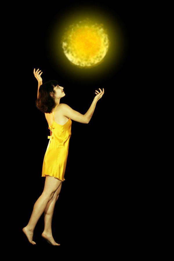 Maeva, la magicienne jaune en nuisette de soie, invoque un soleil. La mini-boule de feu flotte dans les airs et éclaire Maeva de sa puissante lumière.