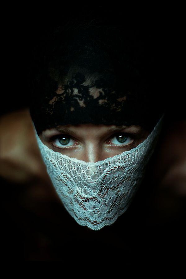 Les yeux verts de Céline sont encadrés entre un rang de dentelle noir qui masque ses cheveux et un rang de dentelle blanche qui masque sa bouche et son nez.