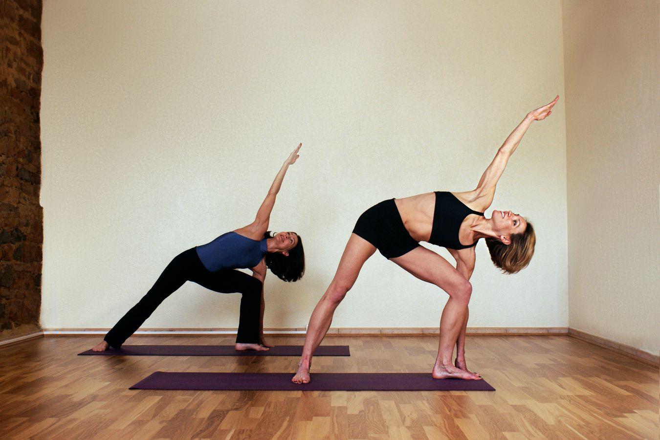 Sydney Martinie donne un cours individuel de Yoga, du Yoga coaching, dans un studio à Lyon. Elle pratique avec son élève un Utthita Parsvakonasana.