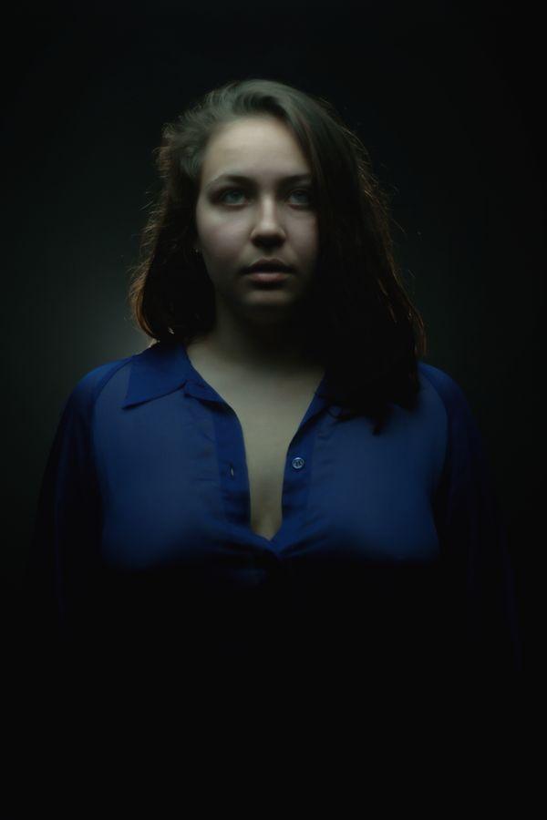 Pour ce portrait, Alice porte une chemise bleu en organza transparente. Elle a le regard perdu dans le vide et fait penser à une héroïne de série télévisée.