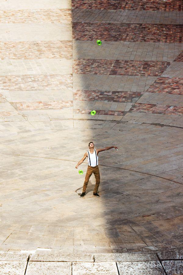 Yohan Durand est entre l'ombre et la lumière sur le parvis de l'Auditorium de Lyon. Le vert de ses 3 diabolos tranche avec les tons orangés du sol.